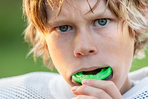 '.$pk.' - young boy wearing athletic gear and putting green mouthguard in his mouth